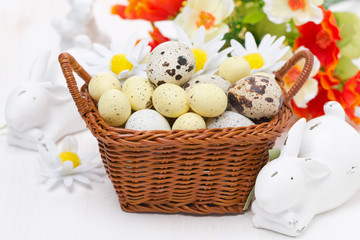 wicker basket with easter eggs and white rabbits