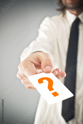 Businessman holding card with printed question mark