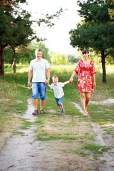 Father, mother and son walking outdoors.