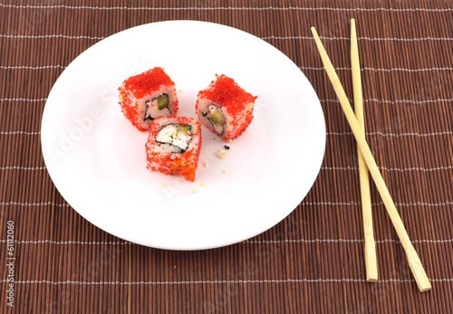 Sushi on plate with chopsticks over wicker straw mat