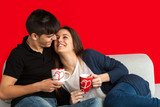Cute couple on couch drinking coffee.