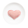 White plate with handmade heart on it isolated on white