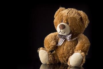 Brown teddy-bear on black background