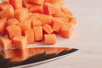 Diced raw carrots with knife on a chopping board