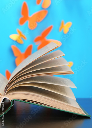 Opened book on wooden table on butterflies background