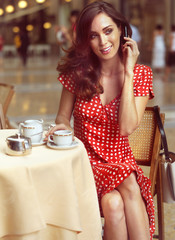 beautiful woman sitting in a Cafe with mobile
