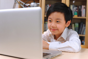 Happy Asian boy in front of computer