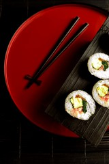 Sushi roll  with chopsticks on Japanese red tray