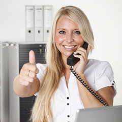 Office assistant has a call at the office, shows thumb up