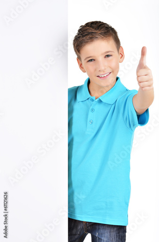 boy looks out from the  white banner with thumbs up gesture