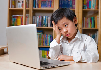 Frustrated Asian school boy in white shirt looking at computer