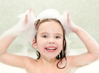 Happy little girl washing in bath with foam