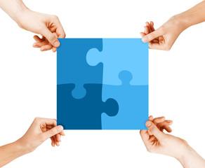 four hands connecting puzzle pieces