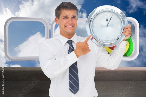 Leinwandbild Motiv Composite image of anxious businessman holding and showing a clo