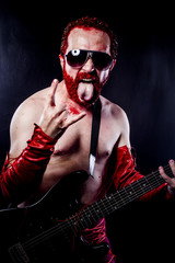 guitarist with electric guitar black, wearing face paint and red