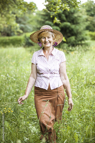 Friendly Senior Peasant Woman in Straw in Meadow Smiling