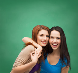 two laughing girls hugging
