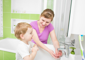 Happy mother and kid washing hands with soap together in bathroo