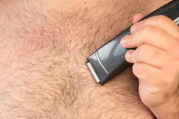 Beharrte männliche Brust und ein Rasierer