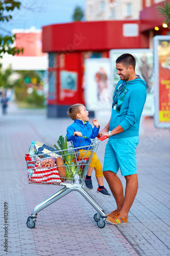 happy father and son after shopping in supermarket