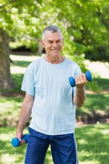 Smiling mature man with dumbbells at park