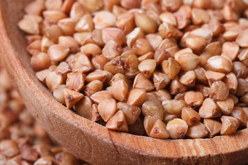 brown buckwheat groats close-up in a wooden bowl