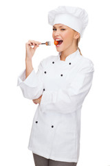 female chef, cook or baker with fork and tomato