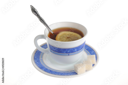 A cup of tea with one slice of lemon within and refined sugar on