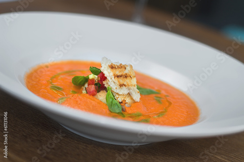 Image of tasty pumpkin soup with crouton and basil served in res