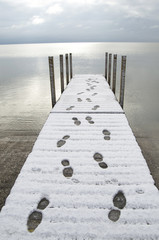 Snow Covered Dock With Human Footprints