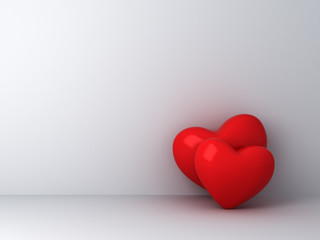 Two red hearts on empty white wall background