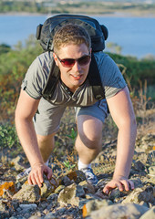 Male tourist with backpack climbs a mountain.