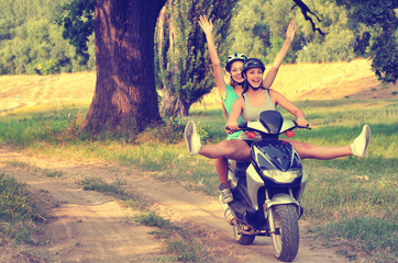 Two teenage girls riding motorcycle