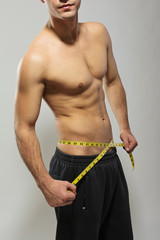 Shirtless fit young man measuring his waist