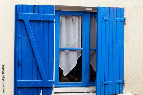 Old window with blue shutters.