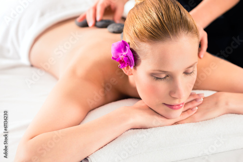 Frau bei Hot Stone Massage im Wellness Spa