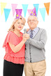 Mature couple with party hats singing on microphone