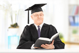 Mature man in graduation gown reading book seated on table