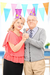 Mature couple with party hats singing on microphone indoors