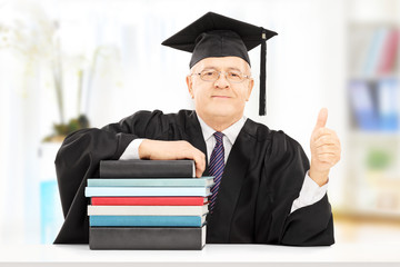 College professor seated on table with books gesturing happiness