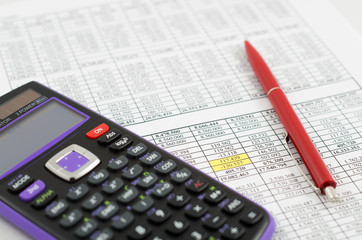 Calculator and pencil on the paper with financial data sheets