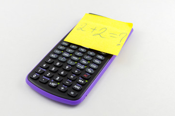 Calculator and yellow sticky note on the calculator