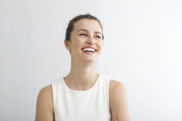 Young woman smiling against white background