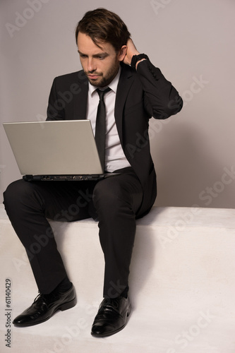Businessman sitting on a stair working on a laptop