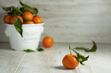 Clementine mandarines with green leaves on gray wooden backgroun