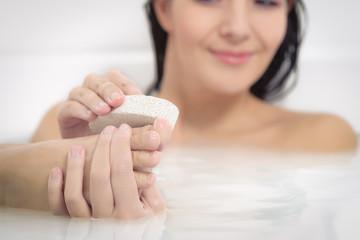 Frau nutzt einen Bimsstein zum Peeling ihrer Füße