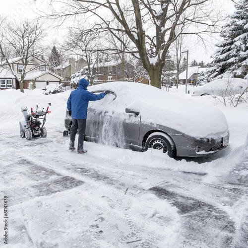 Man Clearing Snow Off a Car Window