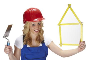 Junge Handwerkerin mit Haus aus Zollstock, Kelle und Bauhelm
