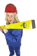 Handwerkerin mit Blaumann und überdimensionaler Wasserwaage