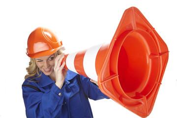 Handwerkerin nutzt Verkehrsleitkegel (Pylon) als Fernrohr